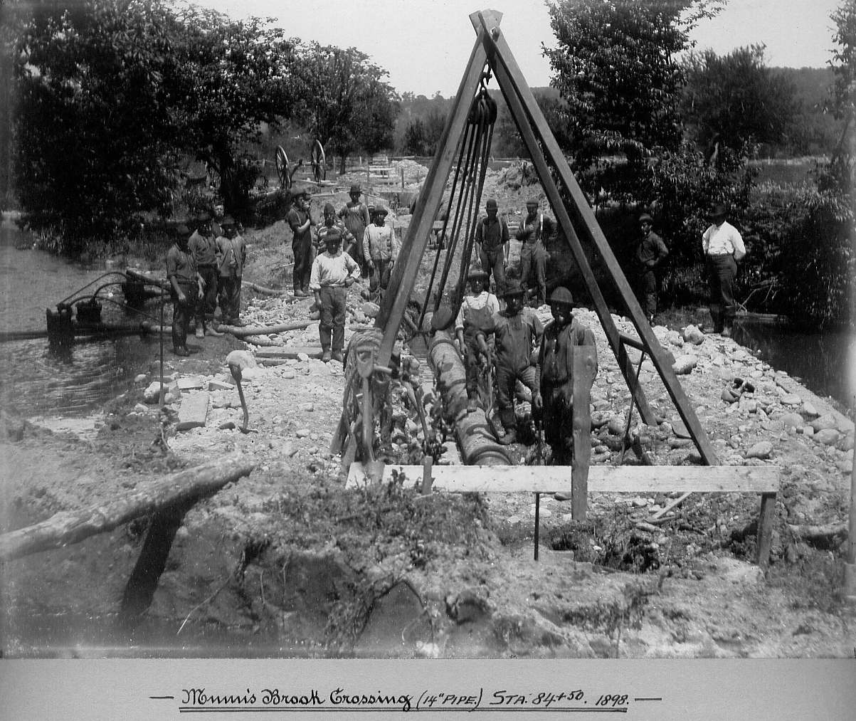 Men laying pipe with rope and pulley