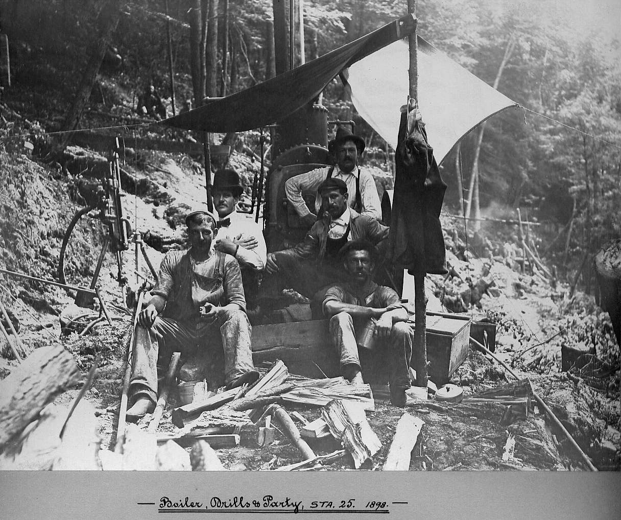 Men sitting with boiler and drills