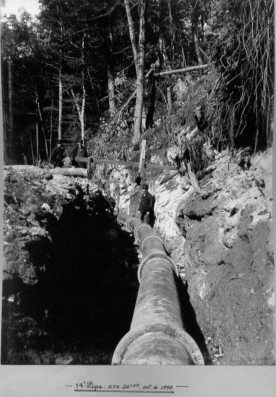 Man in trench with pipe and two men observing pipe