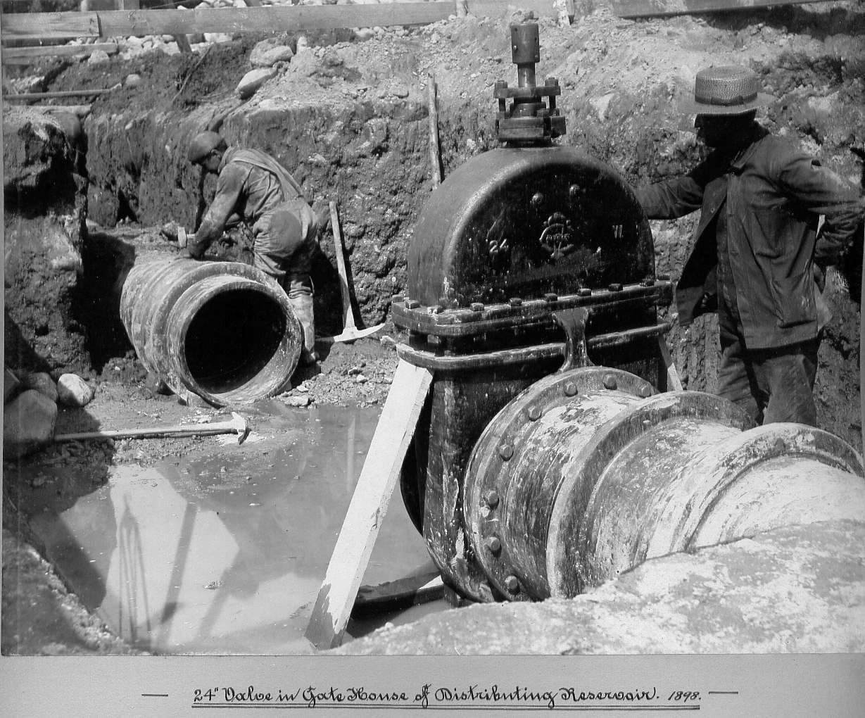 Man laying pipe and man standing next to valve