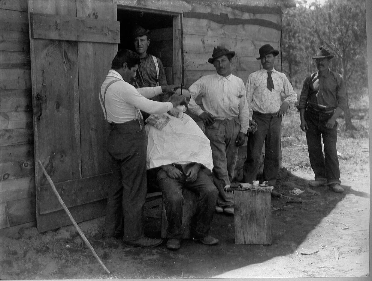 Men standing watching man shaving another man's face
